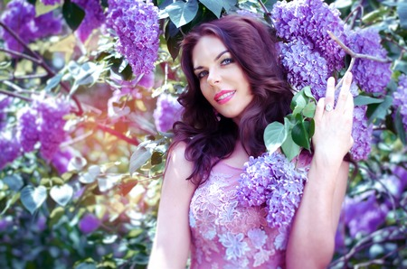 light hair: portrait of an attractive, romantic brunette in a pink dress with a lilac bush blossoms.