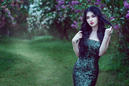 light hair: portrait of a beautiful slim girl with dark hair in a long emerald green dress with bare shoulders is in the spring garden with blooming lilacs.