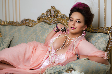 peignoir: beautiful brunette with curvaceous, Rococo hair, rings and beads lies on a beautiful sofa in pink peignoir Stock Photo