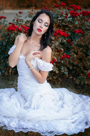 attractive brunette woman in a long white dress, sitting in a bush blooming roses. Stock Photo