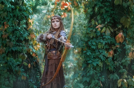 Woman hunter with a bow in hand, taking aim at his prey in the forest.