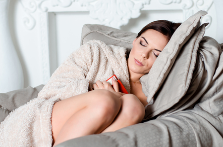 attractive young brunette woman in home bathrobe, fell asleep on an armchair with a book in his hands. Stock Photo