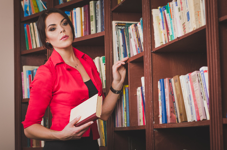 office attire: beautiful young brown-haired woman in office attire standing near bookshelves and chooses the book Stock Photo