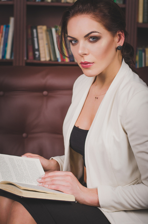 attractive business woman in a business suit sitting on a leather brown sofa in the office and reading a book.