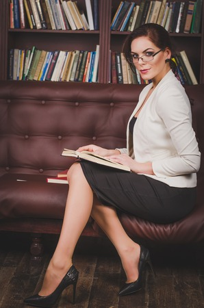 attractive business woman in a business suit with glasses sitting on a leather brown sofa in the office to view, on his knees holding a book with a serious look looks ahead.