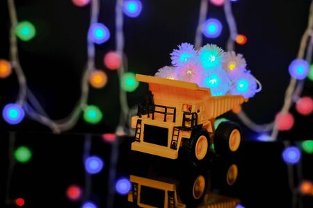 Christmas card. Happy Chrismas Concept. Children's yellow car carries bright festive garlands. Dark background, yellow color.