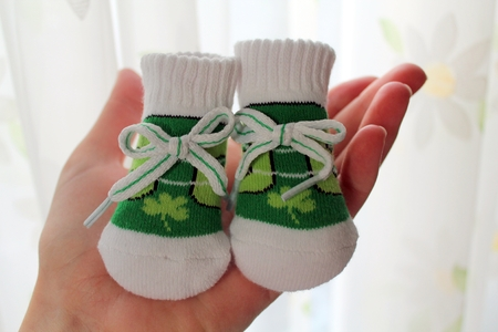 bootees: Tiny green babys bootees with Irish pattern held on a palm Stock Photo