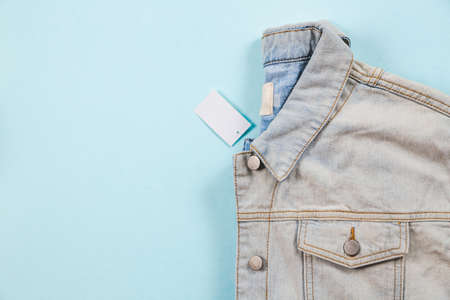 Folded classic denim jacket with a label on a blue turquoise background. Copy space. Sale concept.