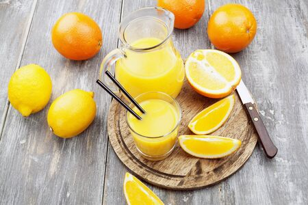 Juice in the jar and oranges and lemons on the wooden table photo