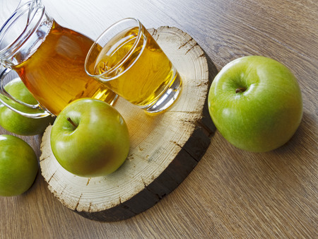 caloric: Apple juice in a bottle on a wooden table