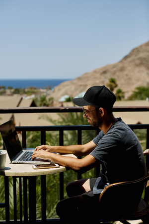 ractive young man with laptop working on the beach freedom remote work freelancer technology Stock fotó