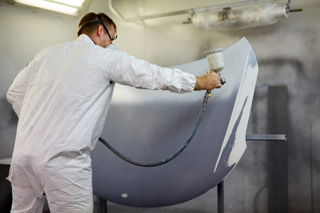 Worker painting a car parts in a paint booth