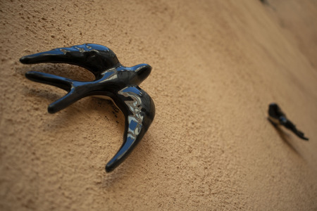 Ceramic swallow animal hanging on the ground color wall Banco de Imagens