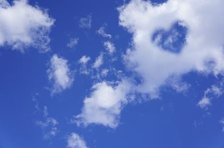 curly headed: The blue sky with white clouds and a cloud in the form of heart  Stock Photo