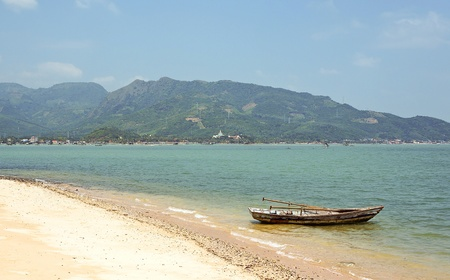 Old boat on the shore of tropical island. Vietnam. photo