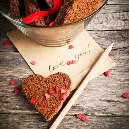 valentine s day: Card with Message Love You in the Letter and Chocolate Cookies in the Shape of Heart at Valentine Day Stock Photo