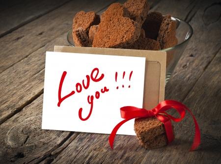 Karte mit der Nachricht Liebe, die Sie in den Brief und Schokoladen-Plätzchen in der Form des Herzens Standard-Bild - 16855359