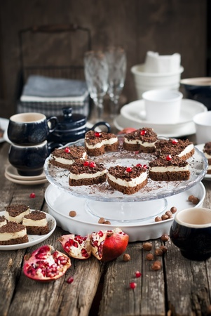 Chocolate Biscuit Cake in the Shape of Heart Decorated with Pomegranate on Festive Table photo