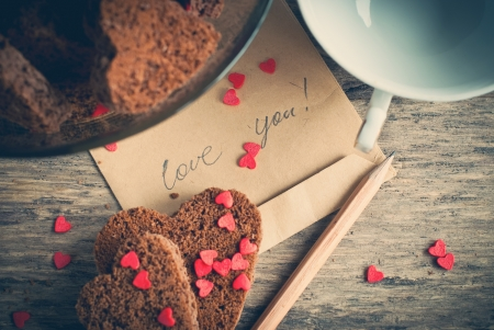 Card with Message Love You on the Letter and Chocolate Cookies Shape of Heart at Valentine's Day photo