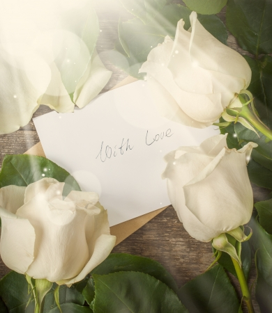 Card with Love Letter Love You and White Roses on the Wooden Table photo