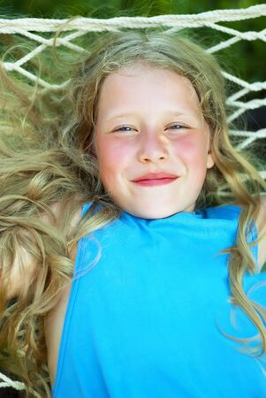 Portrait of the Smiling Girl with a Lon Fair Curly Hair on the Hammock photo