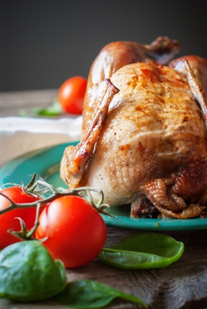 Baked Whole Chicken with fresh tomatoes, close up photo