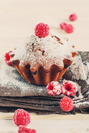 Fruitcake Decorated by Raspberry and icing sugar, toned photo