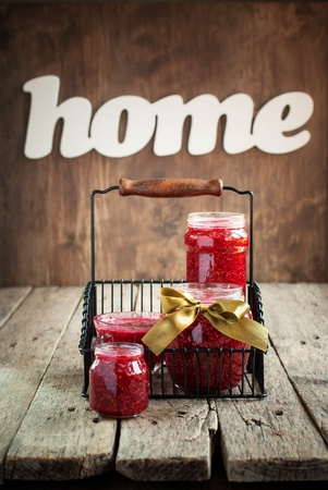 preserving: Raspberry Jam in a jars on the wooden table