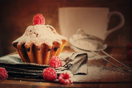 Fruitcake Decorated with Raspberry and icing sugar at the wooden table, tonal Stock Photo
