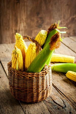 Fresh Corn in a Basket on the wooden table, vertical photo