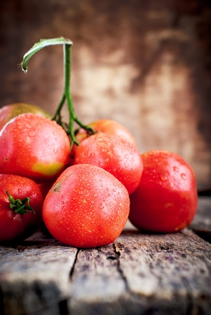 Composition with Tomatoes covered drops on the wooden background