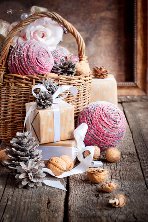 Vintage Christmas Card with Basket, Gifts, boxes, walnuts, balls and pine cones on wooden background photo