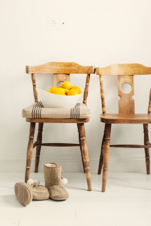 Wooden Chairs in the room, oranges and house slippers, toned