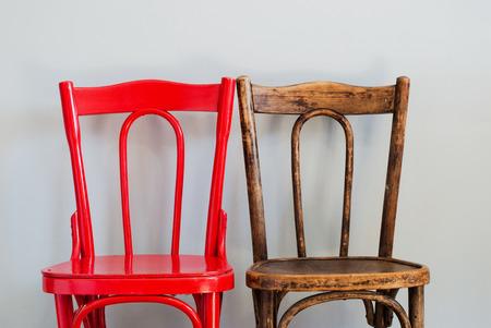 Paar rode en bruine stoelen op een grijze muur Stockfoto