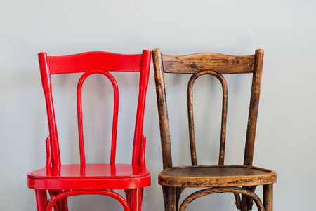 Pair of Red and Brown Chairs on a Grey Wall photo