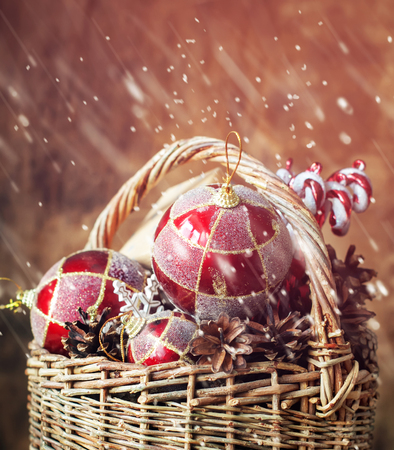 Fairy Tale Christmas Composition with Vintage Gifts in basket. With red balls, pine cones and sweets. Drawing snow, toned effect photo