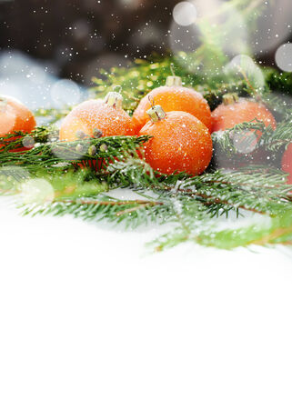 Greeting Card with Tangerines as Fir-tree Toy and Branch of Coniferous on Snow, with boke and snowflakes, isolated on white photo