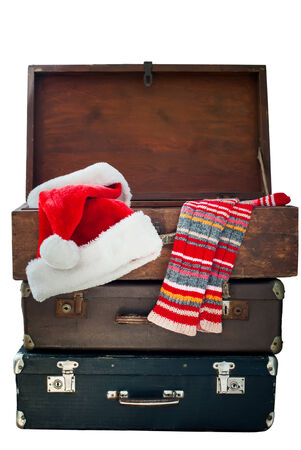 Christmas Santa Claus Caps and Knitting Strips Golfs in Open Wooden Suitcase, isolated on white photo
