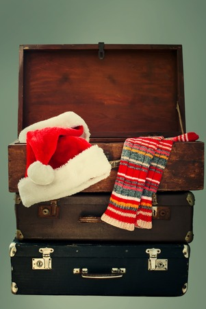 Christmas Santa Claus Caps and Knitting Strips Golfs in Open Wooden Suitcase, toned photo