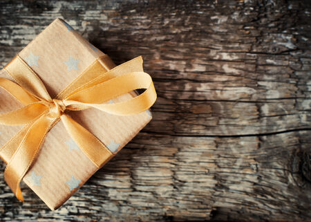 Festive Christmas Box with Beige Ribbon on Wooden Table. Simple style. toned photo