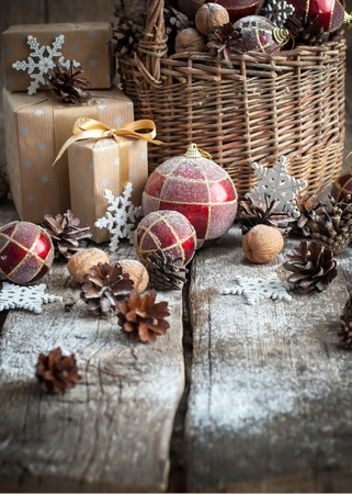 gift basket: Christmas Gifts with Basket, Red balls, Pine cones, Boxes, Snowflakes, Pine cones on Wooden Table. Vintage style Stock Photo