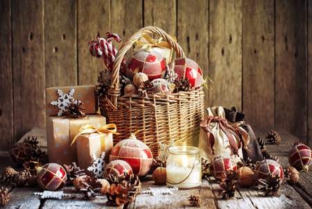 wooden basket: Christmas Basket with Vintage Gifts and Shining Candle. Red balls, Pine cones, Snowflakes, Boxes on Wooden Table. Warm Toned effect