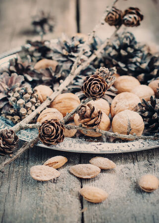 festive pine cones: Close up of Christmas Tray with Pine cones, Walnuts, Almonds, Nuts on Wooden Background, holiday decoration, toned