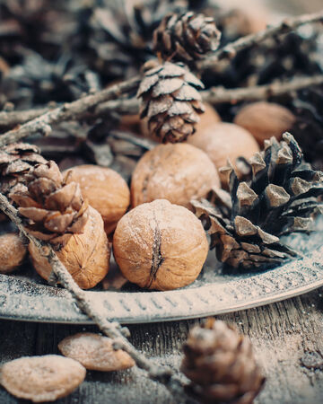 Walnuts, Almonds, Nuts and Pine cones on Wooden Table, holiday Christmas decoration photo