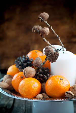 Christmas Composition with Tangerines, Pine cones, Walnuts, Almonds on Wooden Background, holiday decoration photo