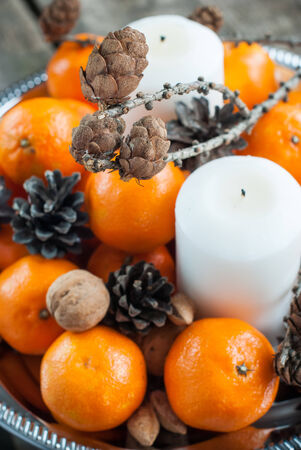 cristmas card: Holiday Composition with Tangerines, Pine cones, Walnuts, Candles and Almonds on Wooden Table, holiday decoration
