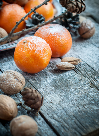 cristmas card: Tangerines, Pine cones, Walnuts and Almonds with snow on Wooden Background, holiday decoration