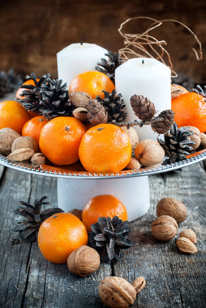 cristmas card: Vintage Christmas Decor for Table with Tangerines, Pine cones, Walnuts on Wooden Background holiday decoration