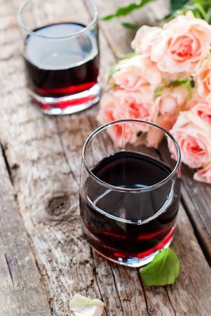 bebes lindos: Naturaleza muerta con vasos de vino tinto y el ramo de rosas rosadas en el fondo de madera Foto de archivo