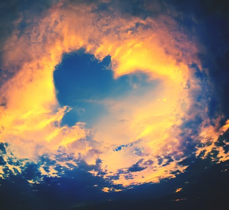 Bright Heaven in a sunset, shape of Heart on blue sky background